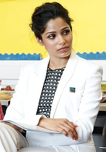 Freida Pinto is sitting with her legs crossed and looking towards her left
