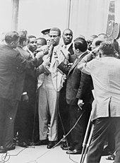 Malcolm X ist von Reportern mit Mikrofonen umgeben, während eine Fernsehkamera die Szene festhält