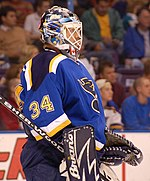 Hockey player in blue uniform with the number 34 on it and goaltender's gear. He faces forward.