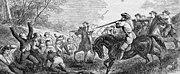Men lined up along a tree line are shot by men on horseback.