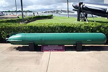 Submarine torperdo on outside display win a naval museum located neat the shore.