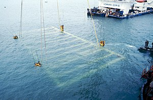 Mary Rose Trust - The final stages of the salvage of the Mary Rose on 11 October 1982. The lifting frame holding the wreck of the Mary Rose can be seen just below the surface of the water, about to be lifted.