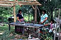 Mary B. Billie and daughter Claudia C. John by a table under a partially built chickee- Big Cypress Reservation, Florida (4348529959).jpg