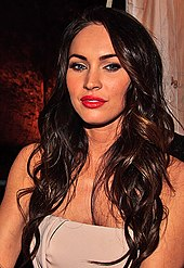 A shot of Megan Fox from the chest up, with dark brown hair.