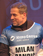 Bandić smiling and looking to his right, wearing blue-and-white skiing jersey over brown long-sleeved shirt