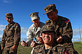 Mongolian Armed Forces Junior Sgt. G. Enkhtuushin, standing right, rehearses a pressure point strike on Junior Sgt. U. Bazarvaani after a demonstration by U.S. Marine Corps Staff Sgt. Alan Stowers, center 130820-M-MG222-006.jpg