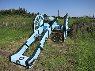 "Photo shows a cannon on a carriage painted light blue and black. There is an open field in front of the gun. In the distance there is a tall smokestack with the lettering, ""St Bernard Port""."
