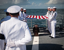 A squad of eight U.S. Navy personnel dressed in all-white uniforms hold a U.S. flag over a casket on the deck of a ship. The casket is carried on a dark wood plinth with several gold-colored badges. Much of the foreground is obscured by a senior officer with his back to us. Beyond is the sea.