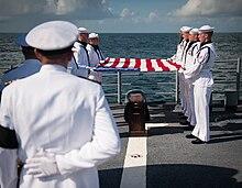 Een team van acht bemanningsleden van de Amerikaanse marine, gekleed in uniforme uniformen, houdt een Amerikaanse vlag boven een kist op het dek van een schip.  De kist wordt gedragen op een donkerhouten plint met verschillende goudkleurige insignes.  Een groot deel van de voorgrond wordt onzichtbaar gemaakt door een hogere officier met zijn rug naar ons toe.  Verder is de zee.
