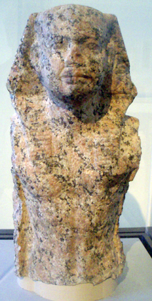 Torso and head of a statue of a king wearing the Egyptian nemes.
