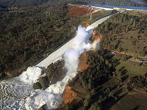 2017 California floods - View of Oroville Dam's main spillway (center) and emergency spillway (top), February 11, 2017. The large gully to the right of the main spillway was caused by water flowing through its damaged concrete surface.