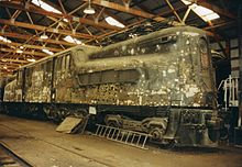 An unpainted, dirty-looking locomotive in a warehouse.