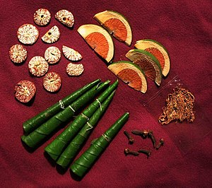 Paan - On display are the items used in a chewing session. The betel leaves are variously folded. Slices of the dry areca nut are on the upper left and slices of the tender areca nut on the upper right. The pouch on the right has tobacco, an optional element. On the lower right, there are dried cloves.