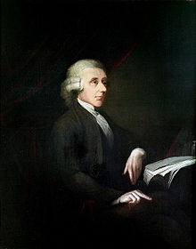 Portrait of a man sitting on a chair and leaning against a table with books and papers.