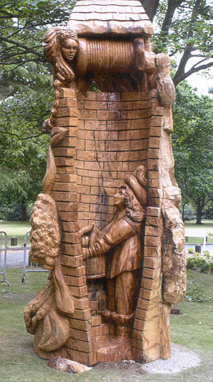 Castanea sativa - A sweet chestnut carved by English artist Steve Field to commemorate the English Civil War, and depicting Prince Rupert hiding from the Roundheads in the well at Wollescote Hall