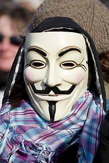 A protester wearing a Guy Fawkes mask, which can be recognized by its pale face, curled mustache, and goatee
