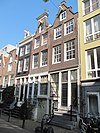 foto van Hoekhuis met hoger opgetrokken voorste stuk onder schilddak. Gepleisterde voorgevel onder rechte lijst