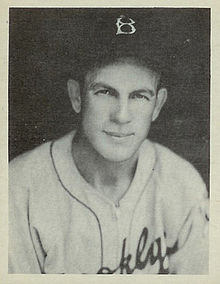 "A man looks into the camera, smiling, while wearing a white baseball jersey and dark cap with a ""B"" on the center."