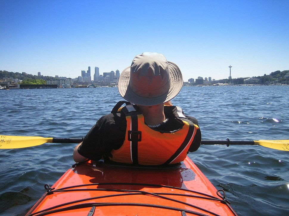 Photo of rear of person wearing orange life preserver sitting in kayak with buildings in far background