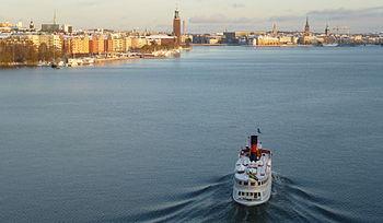Vänster bild: Vy över Riddarfjärden mot öst från Västerbron. Till vänster ligger Kungsholmen, rakt fram syns Stockholms stadshus och till höger därom Riddarholmen. I förgrunden stävar ångfartyget S/S Drottningholm in mot Stadshuskajen.  Höger bild: Vy mot väst från Centralbron med fritidsbåtar som just lämnade Slussen. Längst till höger syns Stockholms stadshus och i bakgrunden skymtar Västerbron.