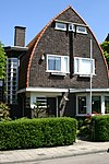 foto van Vrijstaande villa, in Amsterdamse Schoolstijl, deel uitmakend van een samenhangend ensemble van woningen