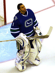 Roberto Luongo in full blue and white Vancouver Canucks goalie uniform and equipment, holding his goalie stick out