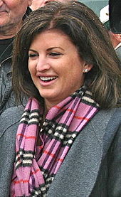 A photograph of a woman facing left and looking left while wearing a pink, black, and white plaid scarf, a grey jacket, and earrings
