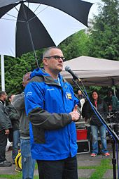 A man behind a microphone stand, wearing glasses and a blue jacket; behind him is a man holding up an umbrella.