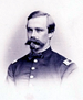 Head and shoulders of a white man with a bushy Van Dyke mustache, wearing a jacket with buttons down the center and rectangular patches on each shoulder.