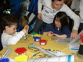 Wellcome Trust Sanger Institute - Children at a public outreach event thread bracelets in four colours to spell out a DNA sequence.