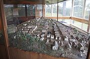 A large table enclosed in glass containing many miniaturized buildings laid out to form a town
