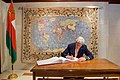 Secretary Kerry, Against the Backdrop of an Omani Rug Depicting a World Map While he Signs the Guestbook (22798780698).jpg