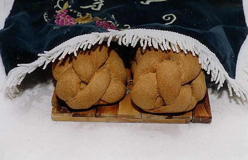 Two braided Shabbat challahs placed under an embroidered challah cover at the start of the Shabbat meal Shabbat Challos.jpg