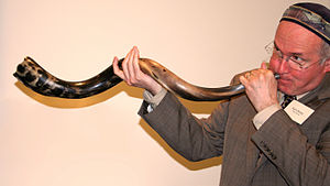English: A man demonstrates sounding a shofar ...