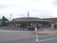 A low circular building with a wide awning is surmounted by a glazed column with a metal ball on the top