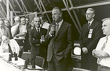 Agnew, standing, speaks into a microphone as others seated in the row of spectators nearby look on.