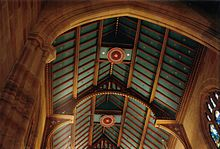 View looking up into the open gabled roof of St Andrews. The beams, rafters and air vents are decorated with bright red rebates and gold leaf details. The ceiling panelling is blue-green dotted with gold stars.