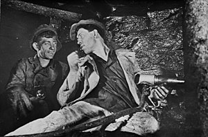 Aleksei Stakhanov and another man at work in a Soviet coal mine. Stakhanov, while holding a drill, is seated at the coal face, his head turned to speak to his colleague.