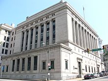 A seven-story sandstone building faced with ionic columns on a city street corner.