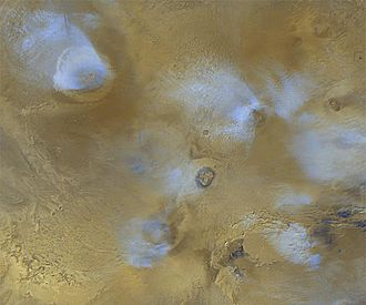 Tharsis - Orographic water ice clouds hover over the volcanic peaks of the central Tharsis region in this color image mosaic from Mars Global Surveyor. Olympus Mons dominates at upper left.  At center are the three Tharsis Montes: Arsia Mons at bottom, Pavonis Mons at center, and Ascraeus Mons at top.