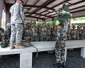 U.S. Army paratroopers demonstrate to Indian Army paratroopers how they bag a T10D parachute in the field.jpg