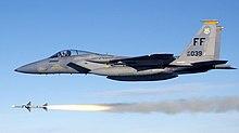 Avión a reacción gris volando por encima del misil tras el disparo del arma.
