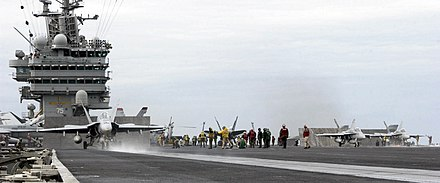 Jet aircraft departing aircraft carrier. A gray-overall aircraft, with blue and yellow fins, has just left the edge of carrier's runway, as evident through the extended landing gear.