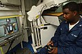 """US Navy 021022-N-5471P-015 Ships Serviceman Third Class Sheikeil Odom relaxes after duty hours by playing a video game in his """"work space"""" aboard the Mobile Bay.jpg"""