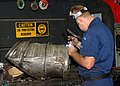US Navy 030618-N-3970R-014 Aviation Structural Mechanic 3rd Class Mathew Stender welds a new flange on an aircraft exhaust manifold.jpg