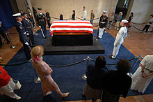 A casket draped with the stripes of the American flag and guarded by military personnel representing each of the five services, as the public files by in single file.
