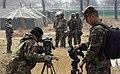 US Navy 050322-F-2902B-192 U.S. Army Spc. Burey, a videographer for AFN Korea, left, and U.S. Navy combat videographer, Photographer's Mate 2nd Class Bradley Sapp, document a simulated enemy prisoner of war camp at Camp Wonju,.jpg