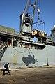 US Navy 051018-N-9288T-004 A crane aboard the dock landing ship USS Pearl Harbor (LSD 52) unloads a piece of heavy equipment from its flight deck in Karachi, Pakistan.jpg