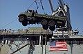 US Navy 051018-N-9288T-091 A crane aboard the dock landing ship USS Pearl Harbor (LSD 52) unloads a piece of heavy equipment from its flight deck in Karachi, Pakistan.jpg