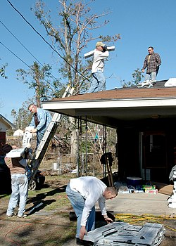 Gulfport, Miss. (Jan. 7, 2006) - Seabees from the Naval Mobile Construction Battalion One (NMCB-1) First Class Association move shingles from the ground to the roof of a house damaged by Hurricane Katrina. NMCB-1 First Class Association makes community service projects its main focus while in homeport. U.S. Navy photo by Photographer's Mate 3rd Class Ja'lon A. Rhinehart.